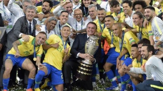 Bolsonaro posa com jogadores e a taça da Copa América